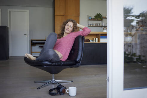 Woman with head in hands sitting on chair at home - RBF08021