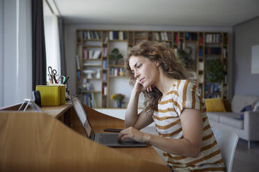 Woman with head in hands working while sitting by desk at home - RBF08030