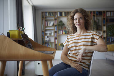 Smiling mid adult woman sitting on chair by desk at home - RBF08033