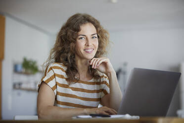 Smiling mid adult woman using laptop while sitting at home - RBF08036