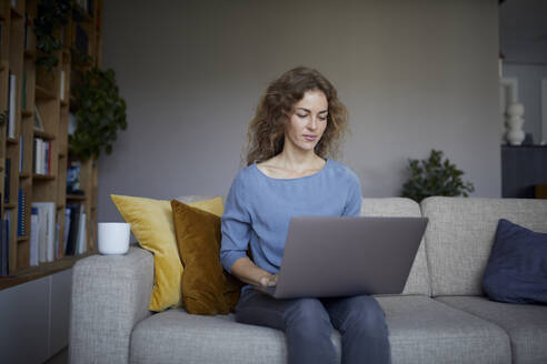 Woman sitting on sofa while working on laptop at home - RBF08045