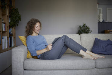 Smiling woman using digital tablet while sitting on sofa at home - RBF08048