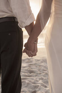 Newlywed couple holding hands while standing at beach - AJOF00170