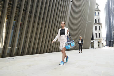 Female professionals walking on footpath in financial district - PMF01287
