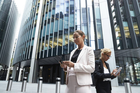 Mature businesswomen using smart phones against modern office skyscraper at downtown district - PMF01296