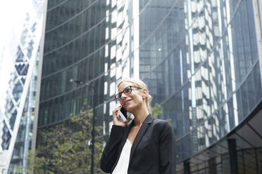 Smiling beautiful businesswoman talking on mobile phone while standing against office building at downtown district - PMF01302