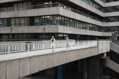 Woman running by female professional talking through mobile phone on footbridge at downtown district - PMF01308