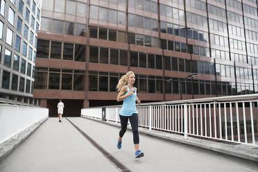 Mature blond woman jogging against businesswoman on footbridge in financial district - PMF01314