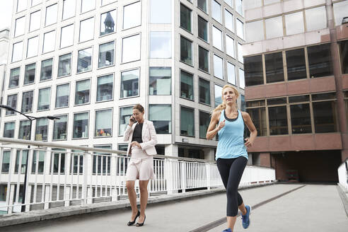 Woman running by businesswoman talking through phone on footbridge against modern office building in city - PMF01317