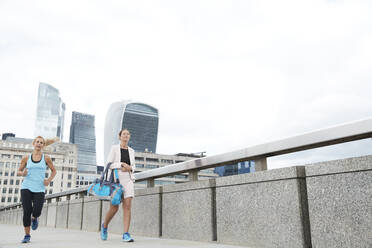Woman running by businesswoman carrying bag on footbridge in city against clear sky - PMF01320