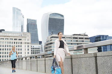 Businesswoman carrying bag while walking ahead of woman jogging on footbridge in city against sky - PMF01323