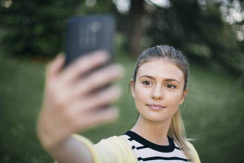 Mid adult woman taking selfie on smart phone while standing in public park - ABZF03426
