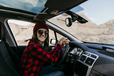 Portrait of female tourist sitting in car and smiling at camera - EBBF00853