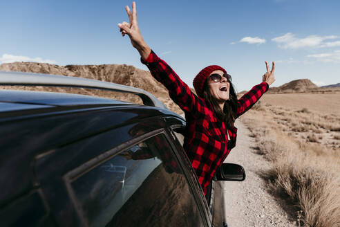 Spain, Navarre, Female tourist leaning out of car window making peace sign gestures over dirt road in Bardenas Reales - EBBF00856