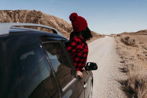Spain, Navarre, Female tourist leaning out of car window over dirt road in Bardenas Reales - EBBF00859