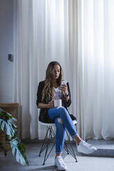 Businesswoman using smart phone while having coffee in office - DCRF00925