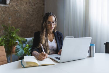 Creative businesswoman using laptop while writing in diary at office - DCRF00928