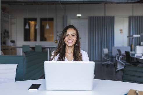Smiling businesswoman with laptop at desk in office - DCRF00946