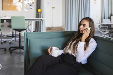 Businesswoman talking on mobile phone while having coffee on sofa in office - DCRF00949
