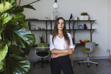 Confident businesswoman standing with arms crossed in office - DCRF00952