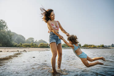 Mother whirling daughter around while standing in water at beach - MFF06255
