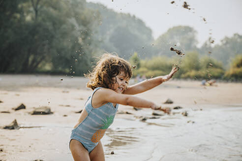 Cute girl throwing sand and mud while standing at beach - MFF06258