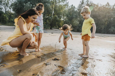 Mature woman and children discovering crab at beach - MFF06276