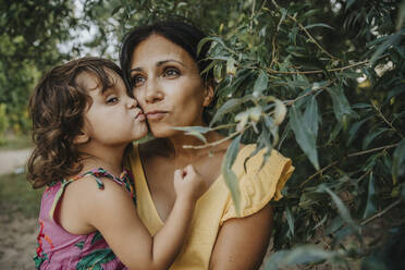 Mother and daughter embracing each other under willow tree - MFF06294