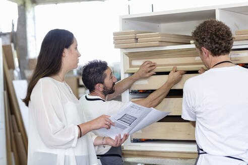 Interior designer and expertise fitting frames in drawer while standing at workshop - EIF00277