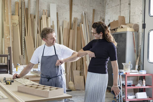 Smiling man and woman giving elbow bump while standing at workshop - EIF00280