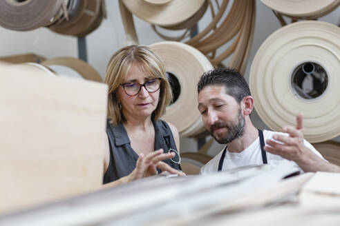 interior designer examining log while standing by coworker at workshop - EIF00283