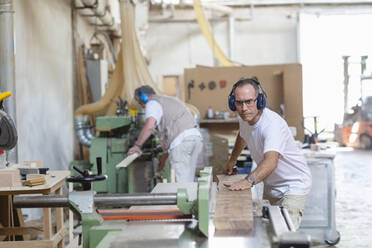 Coworkers wearing earmuff while sawing wood in machine at factory - EIF00298