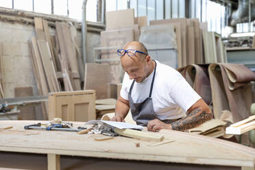 Carpenter reading design in paper while standing at workbench in factory - EIF00301