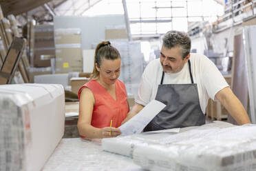 Secretary checking shipment paper while standing by coworker at factory - EIF00316