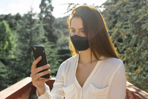 Young woman wearing protective face mask while taking selfie on smart phone - AFVF07315