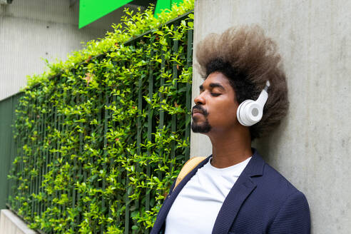 Black man with afro hair leaning against a wall with his eyes closed while listening to music with a wireless headset on the street - ADSF16597