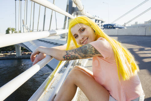 Young woman smiling while sitting on bridge during sunny day - VPIF03158
