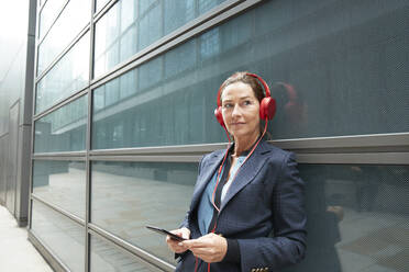 Businesswoman wearing headphones using mobile phone while leaning on building in city - PMF01338