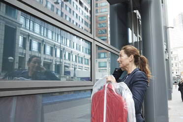 Businesswoman with clothes looking at her reflection while standing in city - PMF01341
