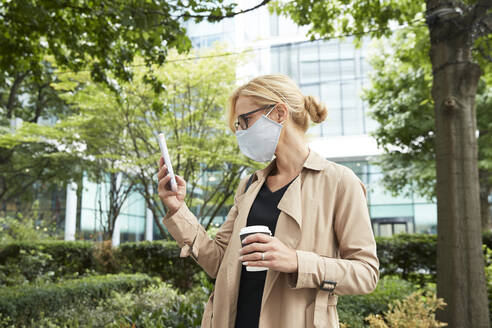 Woman holding coffee cup while using mobile phone in city - PMF01347