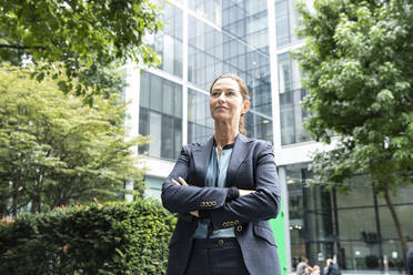 Businesswoman with arms crossed standing at office park - PMF01356