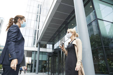 Business people wearing face mask talking while standing with social distance against office building - PMF01368