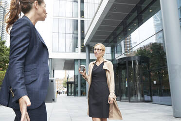 Businesswoman and colleague talking while standing at social distance in city - PMF01374