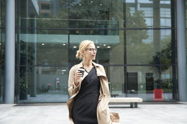Woman holding coffee cup while standing against office building - PMF01377