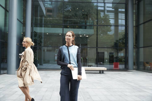 Woman standing and holding laptop with colleague walking in background against office building - PMF01380