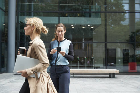 Woman holding laptop while walking with businesswoman using mobile phone in background - PMF01383