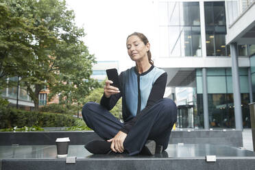 Businesswoman using mobile phone while sitting on bench at office park - PMF01386