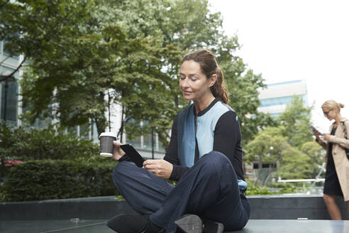 Businesswoman holding coffee cup while using mobile phone with colleague standing in background at office park - PMF01389