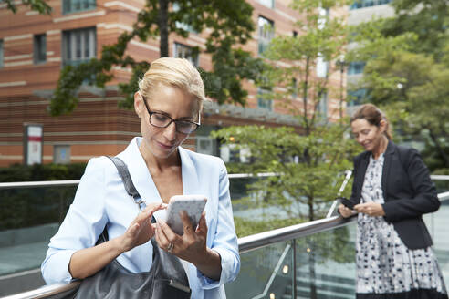 Woman using mobile phone while colleague standing in background at city - PMF01395