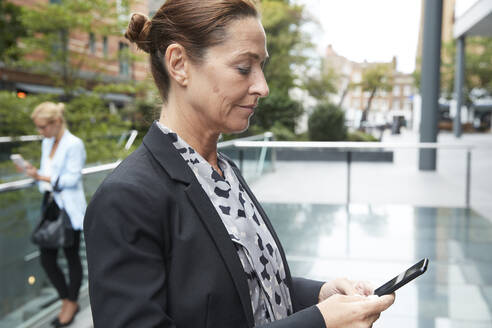 Businesswoman using mobile phone with colleague standing in city - PMF01398